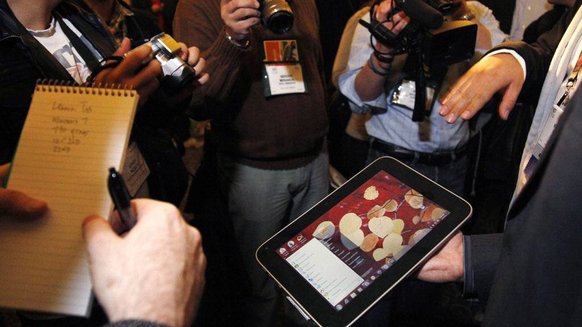 "A man surrounded by journalists displays an unannounced Lenovo tablet computer running the full Windows 7 operating system at a preview of the Consumer Electronics Show (CES) in Las Vegas January 4, 2011. According to a spokesman at the show, the computer, scheduled to be available in May, has a tentative name of the IdeaPad Slate, uses the Intel ""Oak Trail"" 1.6gHz processor chip and has a 32gb SSD drive and a microSD card slot."