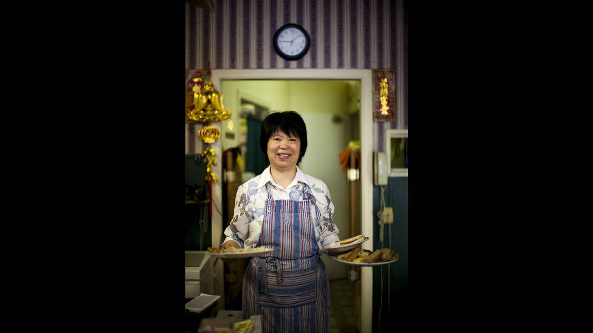 June Huang, owner of the Sunny Spot Cafe, stops for a portrait while serving breakfast to customers at the cafe in the Mount Pleasant neighbourhood of Vancouver, British Columbia, June 30, 2011.