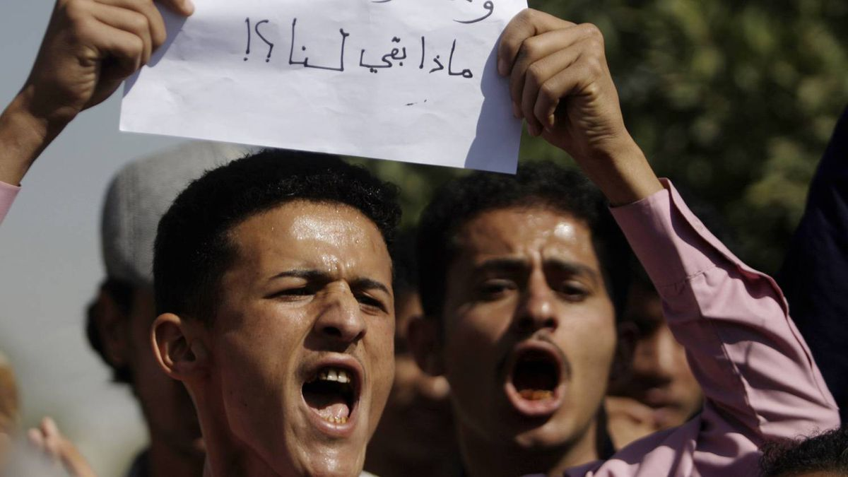 """Anti-government protesters shout slogans during a rally in Sanaa January 22, 2011. The sign reads: """"Our resources are robbed. Our rights are taken. What is left for us?""""."""