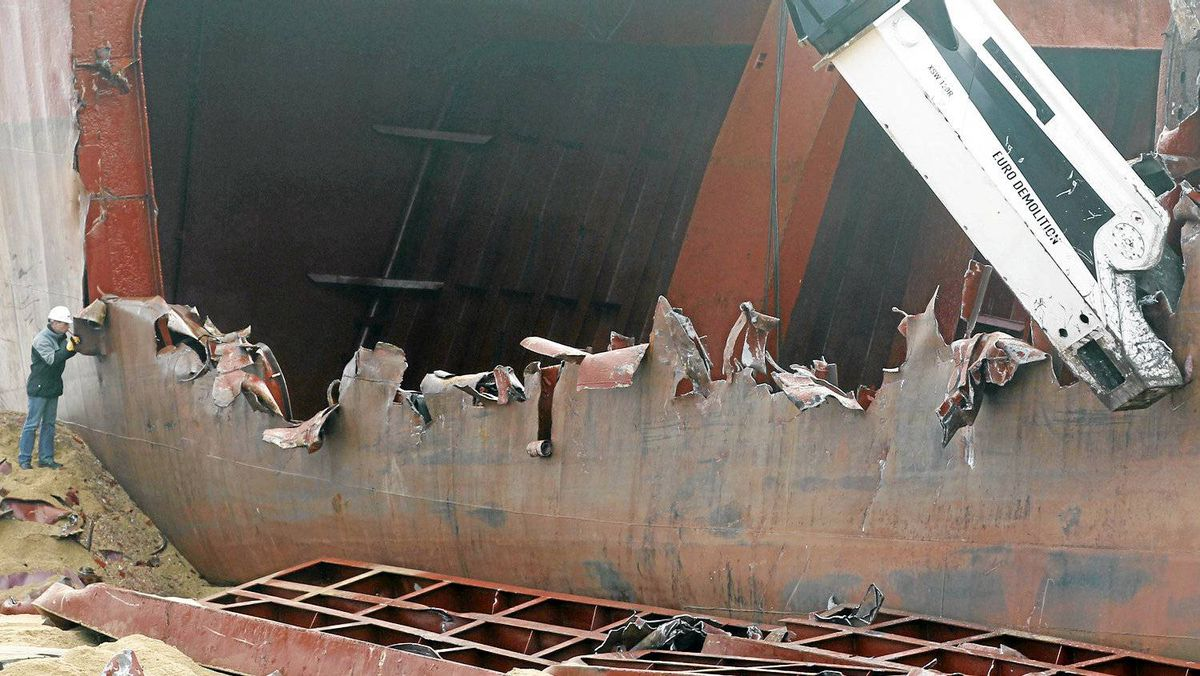 A crane begins to dismantle the Maltese-registered cargo ship the TK Bremen.The 19 crew members on board were airlifted to safety by helicopter and booms deployed to contain an oil spill threatening a nearby beach.