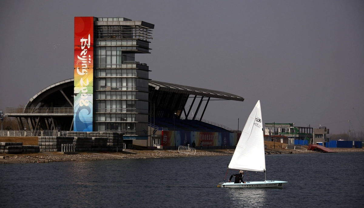 A boat sails past a stand and observation tower at the deserted former venue for the 2008 Beijing Olympic Games rowing competition, located on the outskirts of Beijing March 27, 2012.