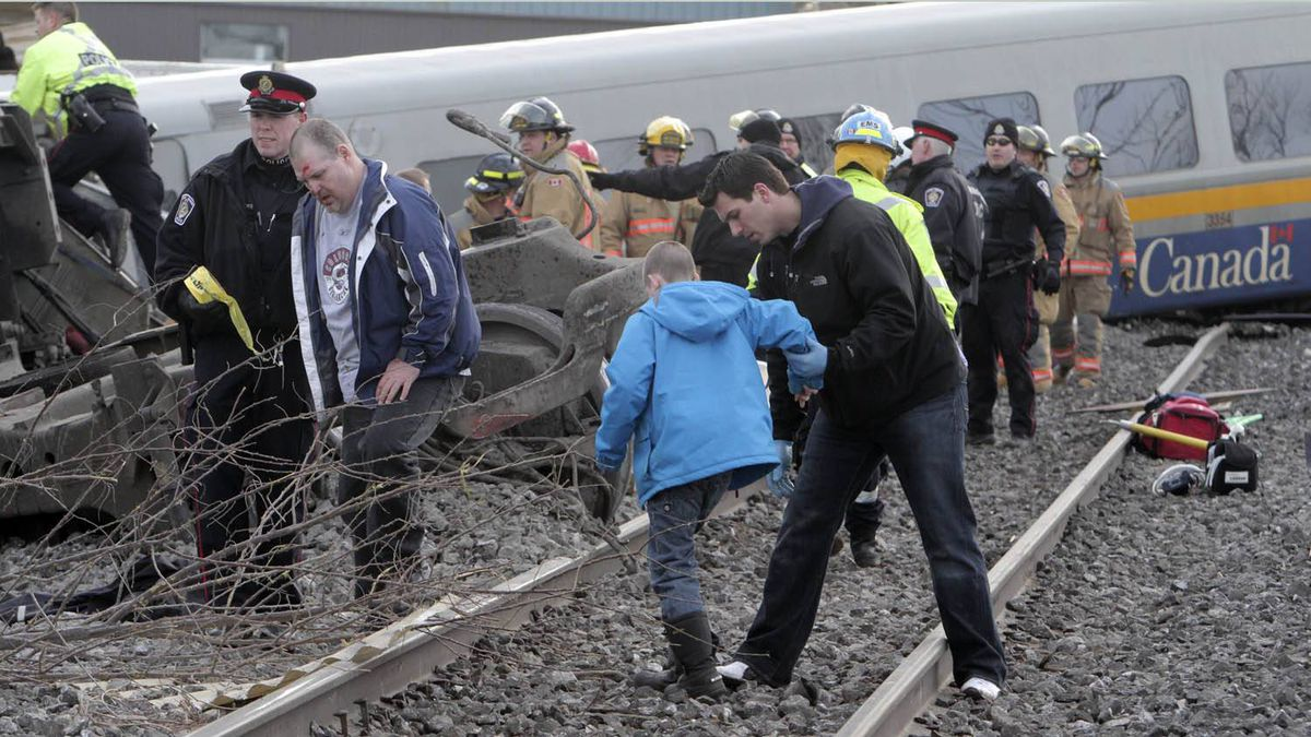 Rescue workers on the scene of a derailed Via train in Burlington help a young boy and his father who were passengers Sunday February 26, 2012.
