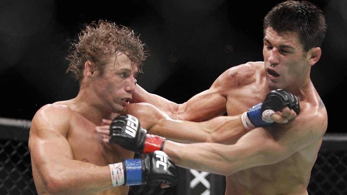 Urijah Faber, left, trades punches with Dominick Cruz during the first round of their UFC bantamweight mixed martial arts title match, Saturday at The MGM Grand Garden Arena in Las Vegas.
