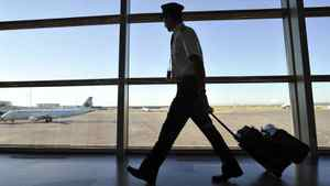 An Air Canada pilot walks to his plane at the International airport in Calgary, September 20, 2011. Air Canada on Friday warned travellers of flight disruptions, saying some pilots are staging an illegal walkout.