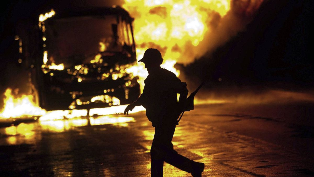 A man runs near a burning bus as residents of the Pinheirinho slum in Sao Jose dos Campos, Brazil, brace for police to arrive to evict them. Some 1,500 families have been occupying private land for the past eight years.
