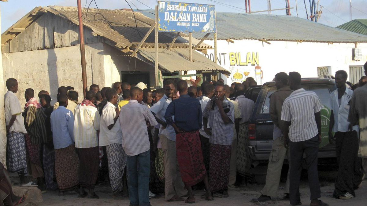 People gather outside a former local bank, where pirates were dividing ransom payment obtained for the freeing of the Spanish ship Alakrana, as they wait to collect their money in Haradheere