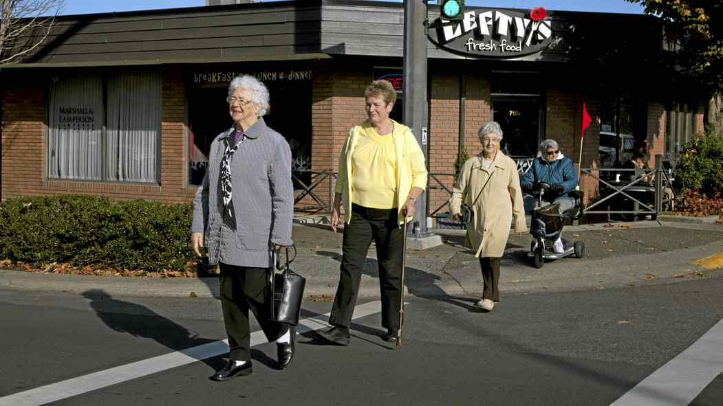 Seniors Sophia Thornley-NIx (left,) Wendy Haines (with the cane and yellow top) , Joan Grange (beige coat and brown pants, and Dorothy Bennett (on the scooter ) cross the street near the Qualicum Beach Seniors Centre on Oct. 24, 2011.