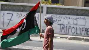A Libyan rebel fighter carries the Kingdom of Libya flag in Tripoli August 23, 2011.