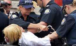 A woman is arrested as she was waiting outside Toronto's detention centre during the G20 summit.