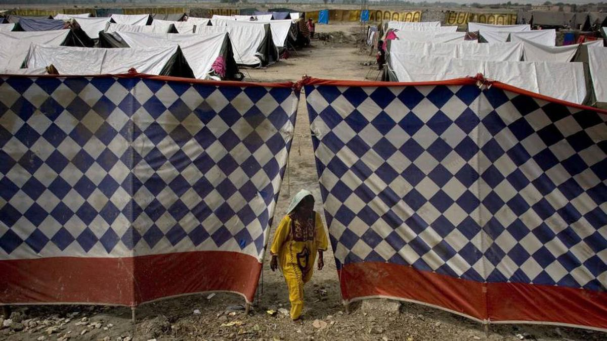 A women steps out through a gape between tents at a camp for flood-affected people in Sukkur, Pakistan on Tuesday, Aug. 31, 2010. Floodwaters that have devastated Pakistan for five weeks headed to the Arabian Sea on Tuesday after swallowing two final towns, but the challenges of delivering emergency aid to 8 million people remained.