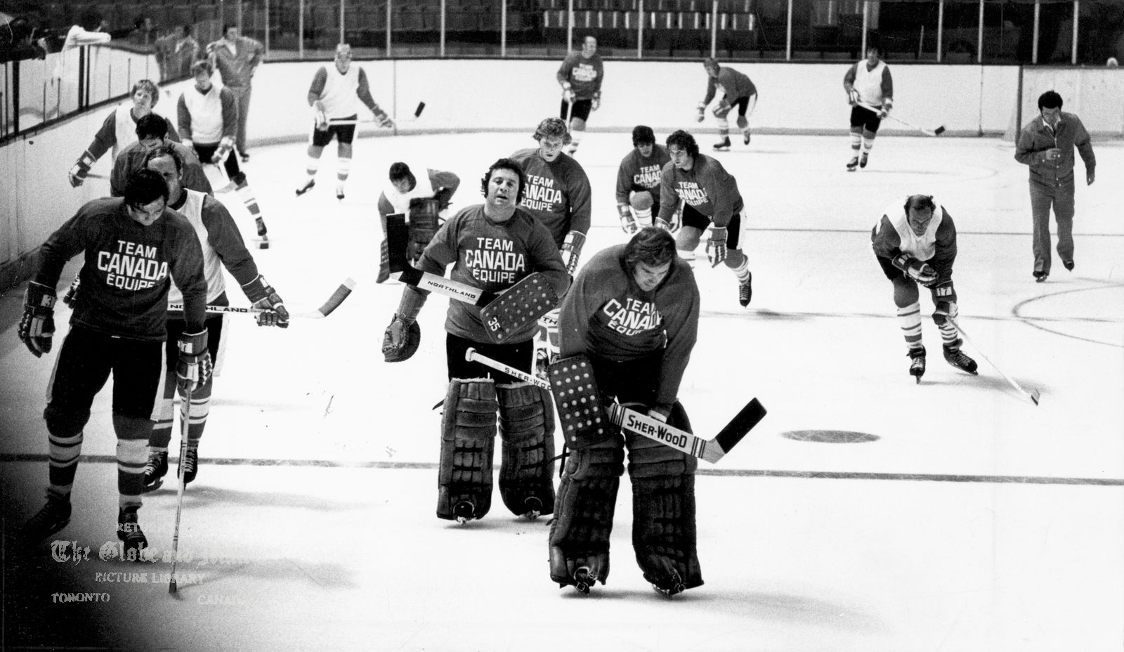 AUGUST 14, 1972 -- TORONTO -- TEAM CANADA TRAINING CAMP -- Jocelyn Guevremont, Vancouver Canucks (left); and goaltenders, Tony Esposito, Chicago and Ken Dryden, Montreal, lead Team Canada players around the boards in opening workout of Team Canada, August 14, 1972 in Toronto. Behind Guevremont are, Dennis Hull, Frank Mahovlich, Pat Stapleton, Wayne Cashman, Gord Berenson and John Ferguson, assistant coach. Following Esposito, Bobby Clark, Michel Larocque (kneeling), Gary Bergman. Behind Dryden, Bill Harris, Dale Tallon and Vic Hadfield. Series starts Sept. 2, 1972 in Montreal. Photo by Barrie Davis / The Globe and Mail. Originally published August 15, 1972