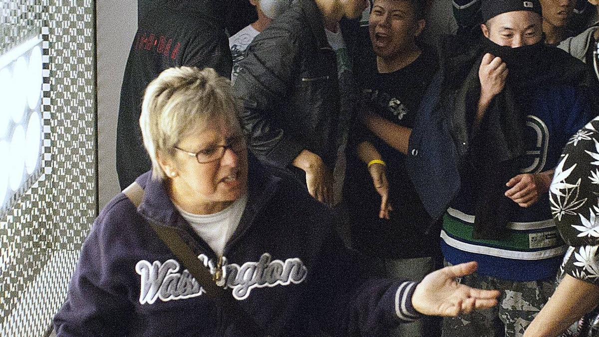 Who is this woman? Help us identify who confronted a crowd in front of the Holt Renfew on Granville Street in Vancouver. The windows were smashed during rioting after the Canucks' 4-0 loss to Boston in game 7 of the Stanley Cup championship.