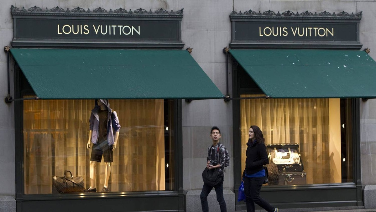 Pedestrians walk past a Louis Vuitton store in downtown Vancouver, Tuesday, March 8, 2011.