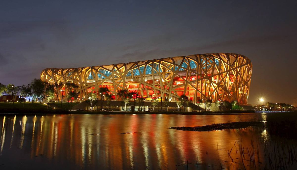 The Bird Nest National Stadium lit up for a rehearsal of the opening ceremony is reflected in a pool of water in Beijing, China, Wednesday, July 16, 2008. Full dress rehearsals are conducted under a cloak of secrecy ahead of one of the most anticipated summer Olympic Games. (AP Photo/Ng Han Guan)