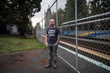 Michael Avery poses for a photograph as a SkyTrain passes by a service gate approximately 100 metres from his home on Stainsbury Ave., in Vancouver, on Oct. 7, 2019.
