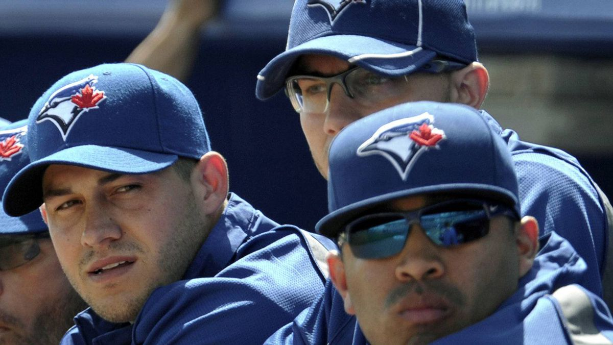 Toronto Blue Jays starting pitchers Dustin McGowan (L), Brett Cecil (C) and Ricky Romero (R) watch from the dugout before their MLB Grapefruit League baseball game against the Boston Red Sox in Dunedin Florida, March 7, 2012. REUTERS/Mike Cassese