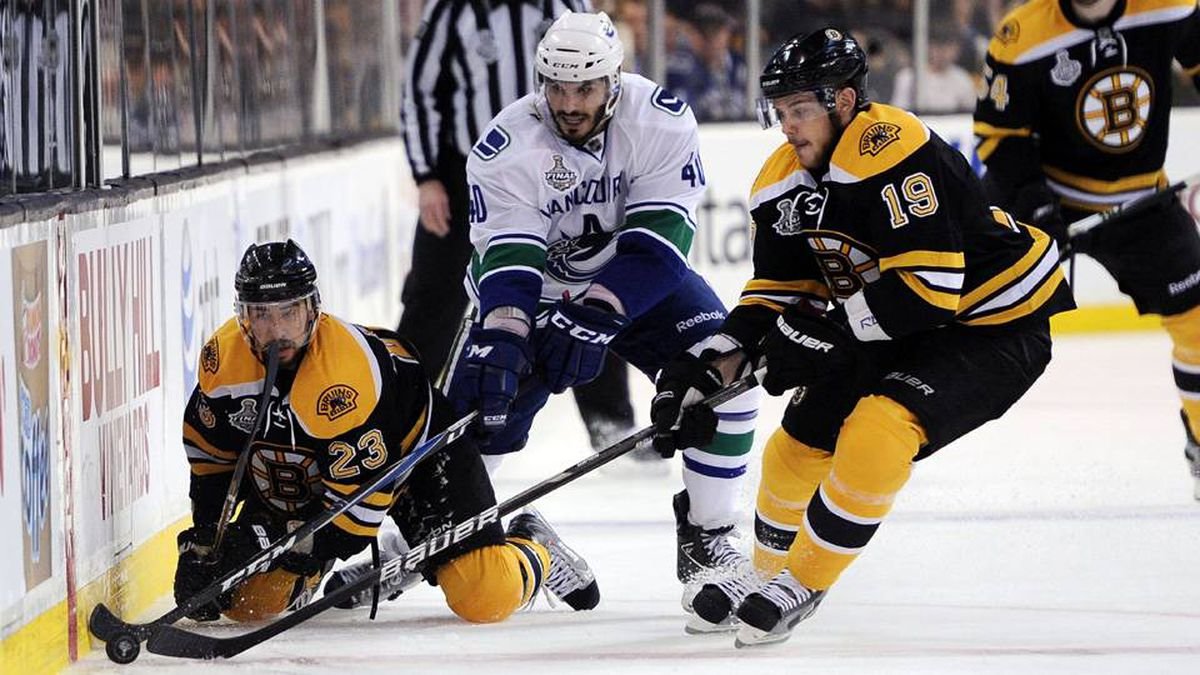 Chris Kelly, left, and Tyler Seguin of the Boston Bruins fight for the puck against Maxim Lapierre of the Vancouver Canucks.