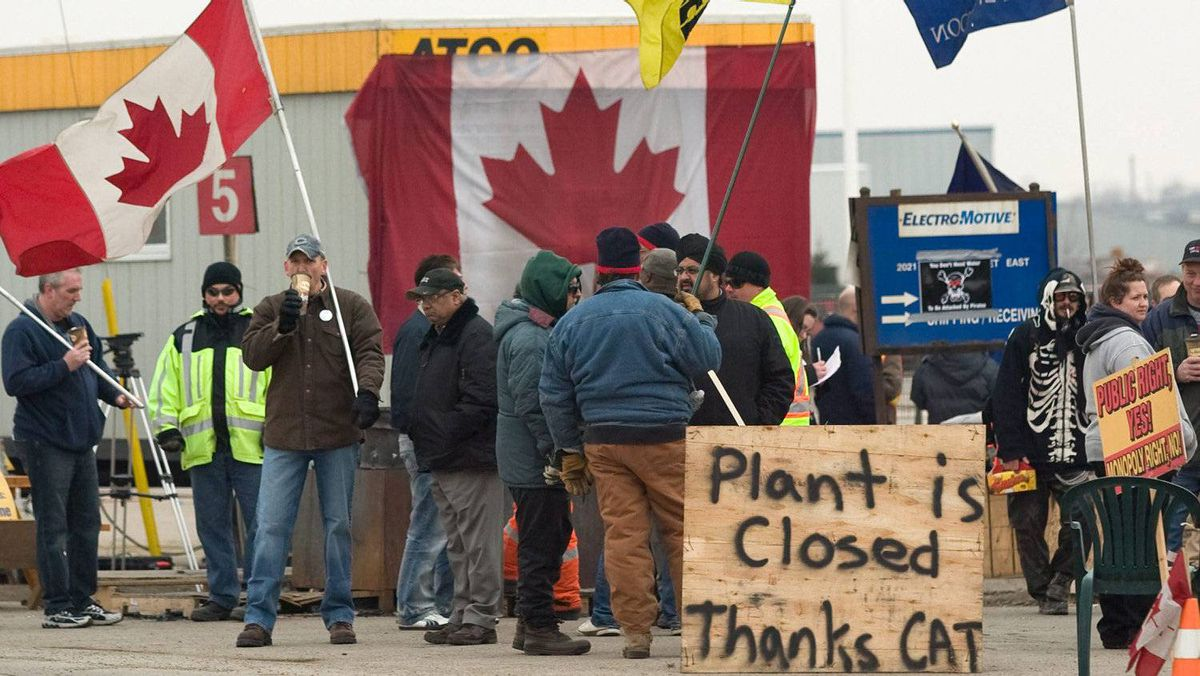 CAW workers picket outside at the Electro-Motive plant in London, Ont., on Feb. 3, 2012, the same day that U.S.-based heavy equipment maker Caterpillar Inc. announced it was closing the plant and moving its production to Indiana.