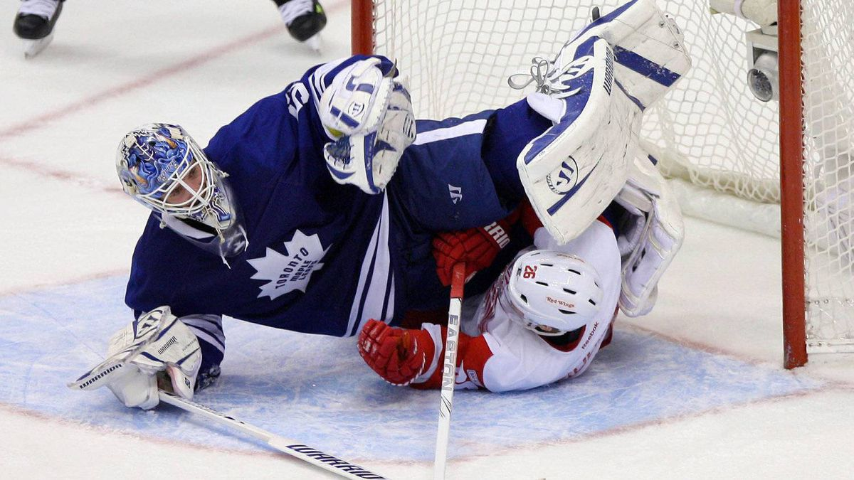 Toronto Maple Leafs goalie Jonas Gustavsson (50) is upended by Detroit Red Wings center Jiri Hudler (26) at the Air Canada Centre. The Maple Leafs beat the Red Wings 4-3. Tom Szczerbowski-US PRESSWIRE