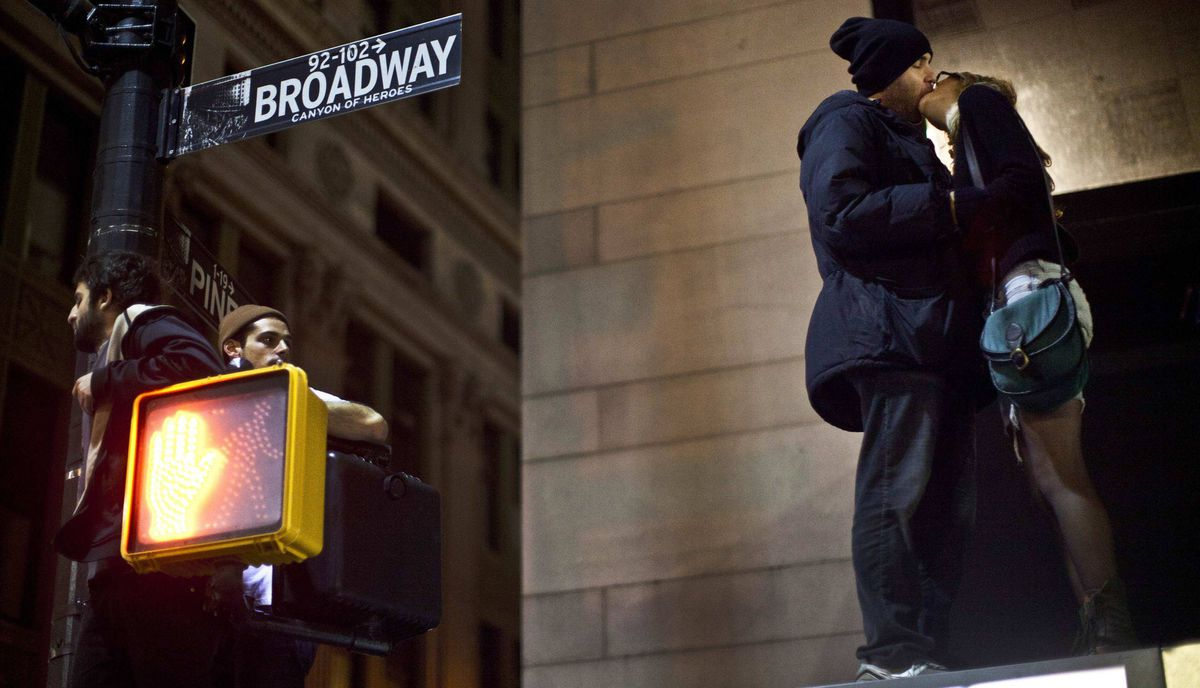 Protesters affiliated with the Occupy Wall Street movement kiss while standing on top of a bus stop during an unannounced raid by the New York City Police Department outside Zuccotti Park in New York, in the early hours of November 15, 2011.