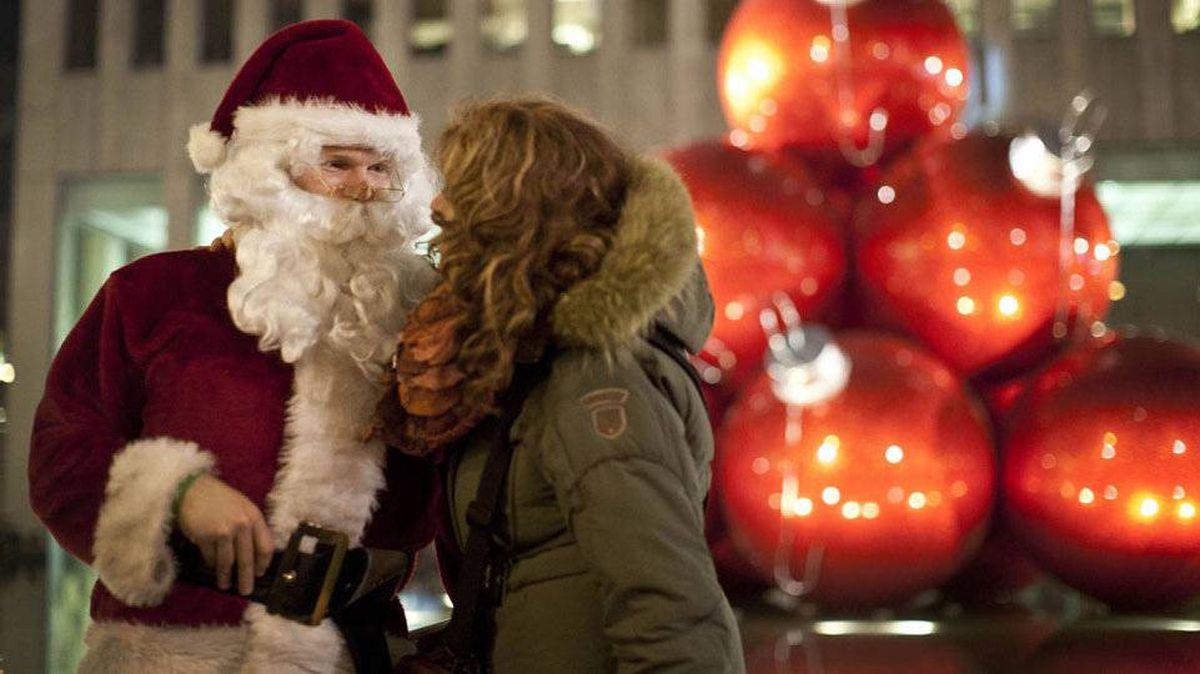 Santa chats with a young woman on West 49th Street in New York.