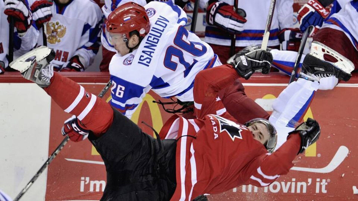 Team Russia's Ildar Isangulov (26) and Canada forward Boone Jenner (20) fight for control of the puck during second period semi-final IIHF World Junior Championships hockey action in Calgary, Alta., on Tuesday.