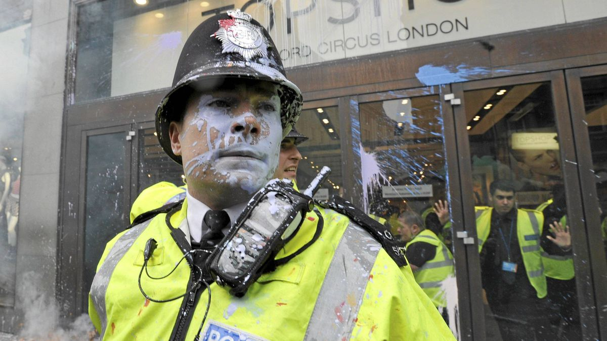 Police officers are splashed with paint in Oxford Street, during a protest organised by the Trades Union Congress, called 'The March for the Alternative,' in central London March 26, 2011.
