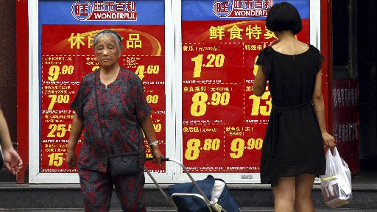 Shoppers walk past and look at a board displaying food prices at a shopping mall in central Beijing, in this August 9, 2011 file picture. China's annual inflation rebounded sharply in March to 3.6 percent, driven by rising food prices, data showed on April 9, 2012.