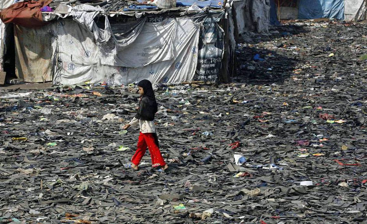 "A girl walks on a creek covered with rubber scraps in Mumbai November 23, 2009. The biggest climate talks in history opened on December 7, 2009 with a stark U.N. warning of the risk of desertification and rising seas and an assurance by hosts Denmark that a deal to combat climate change was ""within reach""."