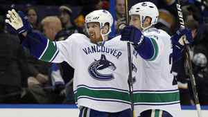 Vancouver Canucks' Daniel Sedin, left, of Sweden, is congratulated by Alexander Edler, also of Sweden, after scoring in overtime of an NHL hockey game against the St. Louis Blues Thursday, Jan. 12, 2012, in St. Louis. Vancouver won 3-2.