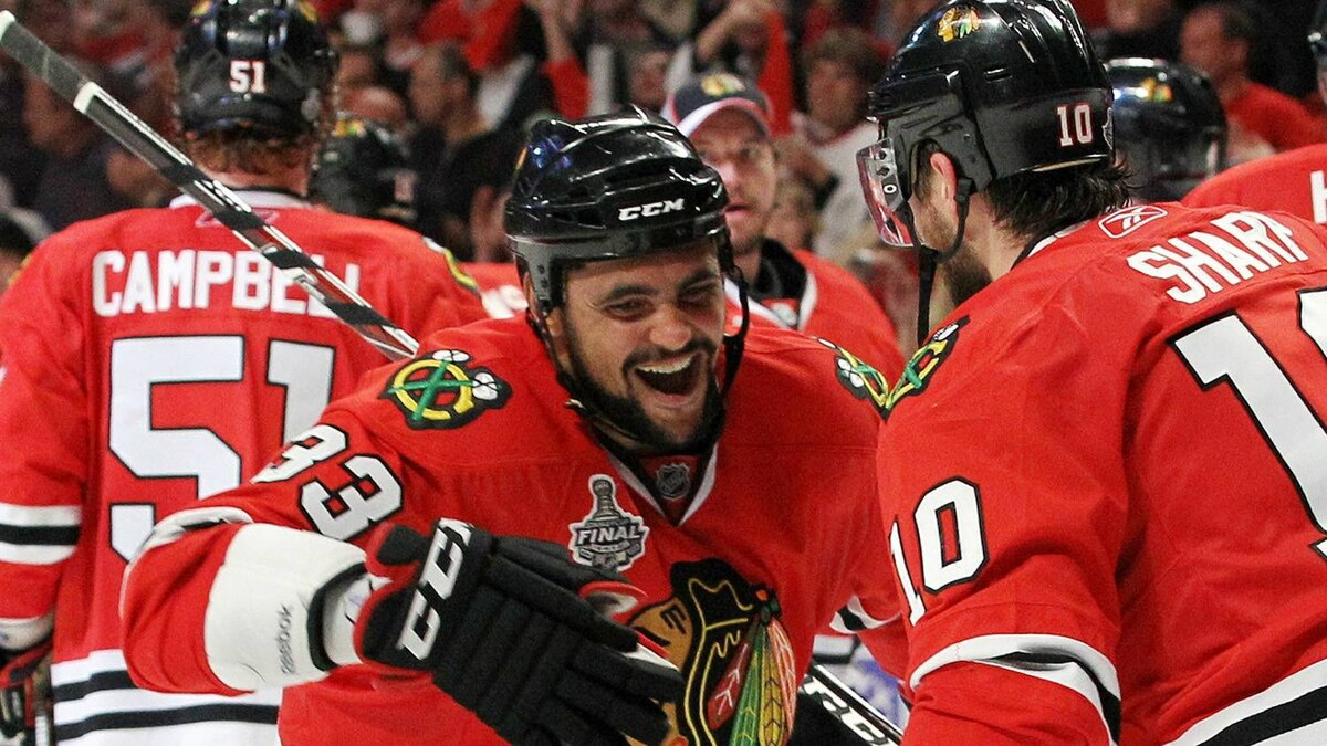 Patrick Sharp #10 and Dustin Byfuglien #33 of the Chicago Blackhawks celebrate after Byfuglien scored the game-winning gaol to defeat the Philadelphia Flyers 7-4 in Game Five of the 2010 NHL Stanley Cup Final at the United Center on June 6, 2010 in Chicago, Illinois. (Photo by Bruce Bennett/Getty Images)