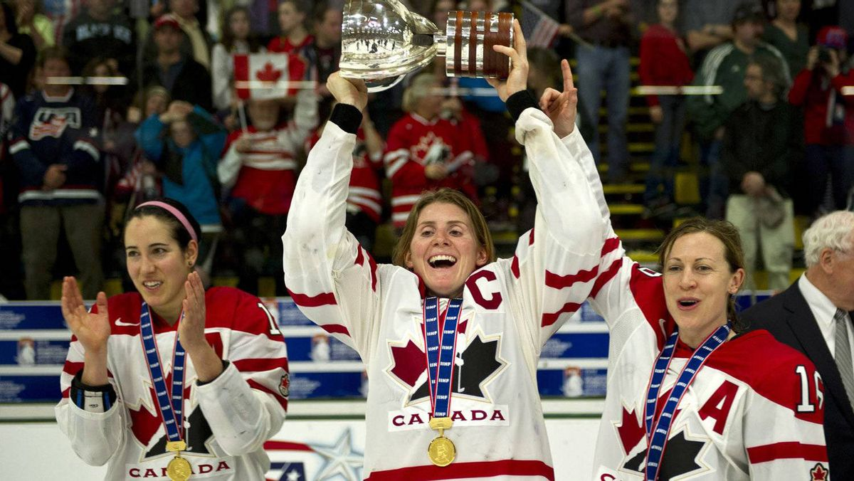 Team Canada captain Hayley Wickenheiser hoists the championship trophy with the help of teammates Caroline Ouellette, left, and Brianne Jenner after defeating Team USA in the gold medal final game at the World Women's Ice Hockey Championships Saturday, April 14, 2012 in Burlington, Vermont. THE CANADIAN PRESS/Paul Chiasson