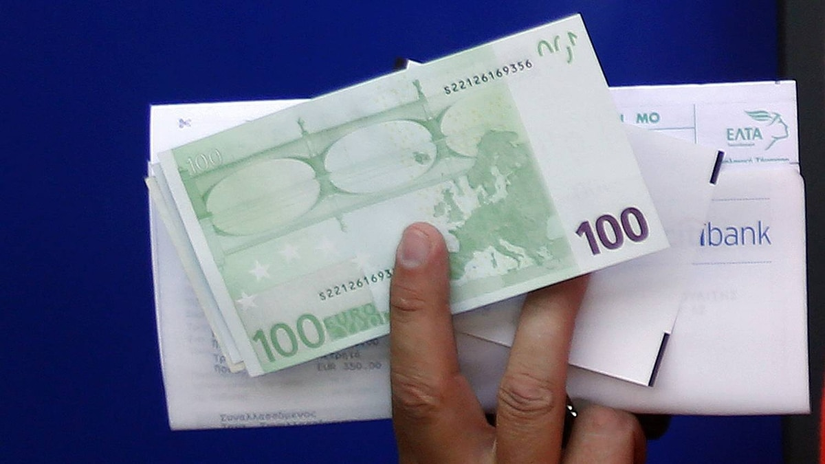 A Greek man holds 100 Euro bills which he just withdrew from an ATM