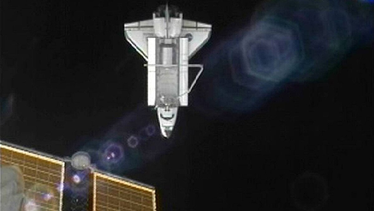 The U.S. space shuttle Atlantis is seen with a solar panel of the International Space Station in the foreground as it departs the station in this still image taken from NASA TV on July 19, 2011.