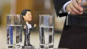 A Stephen Harper bobblehead doll rests on the podium as the Prime Minister announces the creation of the Red Tape Reduction Commission in Toronto on Jan. 13, 2011.