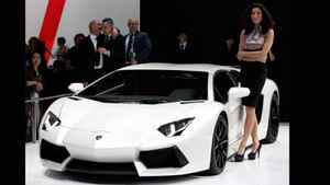 A model stands next to a Lamborghini sports car at Auto China 2012 in Beijing. Global car makers are counting on China to maintain growth in their premium offerings, even as all the signs point to an overall slowing in the world's largest auto market.