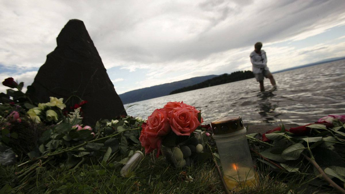 A candle is lit in commemoration of the victims of a shooting as a person walks through a lake near the Utoeya island in Sundvollen July 29, 2011.