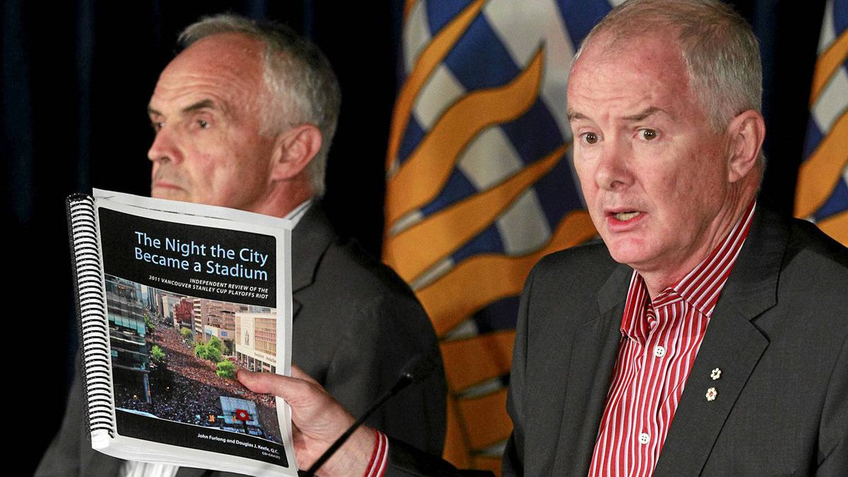 Douglas Keefe, left, and John Furlong display their report on the Stanley Cup riot at a news conference in Vancouver on Sept. 1, 2011.