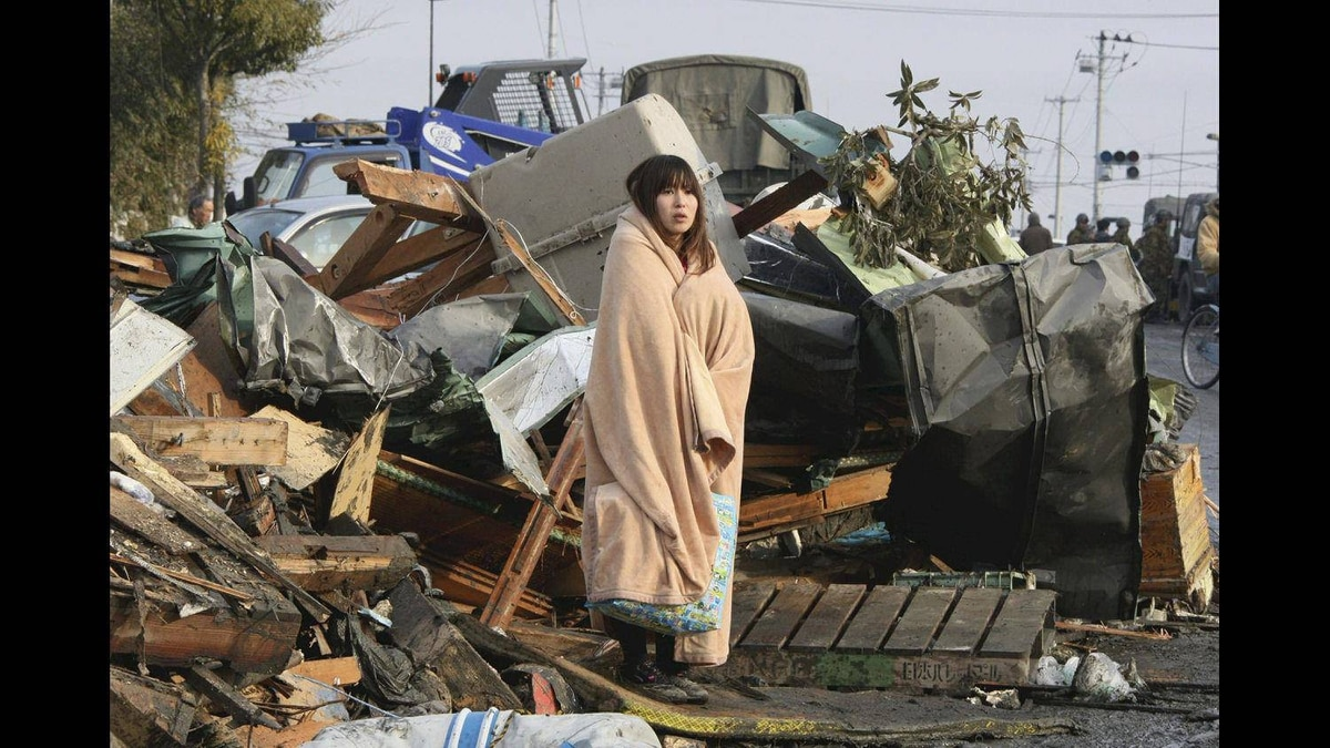 A woman wrapped up in a blanket stands in the middle of rubble, looking at the city submerged under water in Ishinomaki in Miyagi Prefecture (state),March 13, 2011, two days after the catastrophic earthquake-triggered tsunami hit the northeastern Japan.