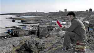 John Mutford reads a book overlooking Yellowknife Bay in Yellowknife, N.W.T.