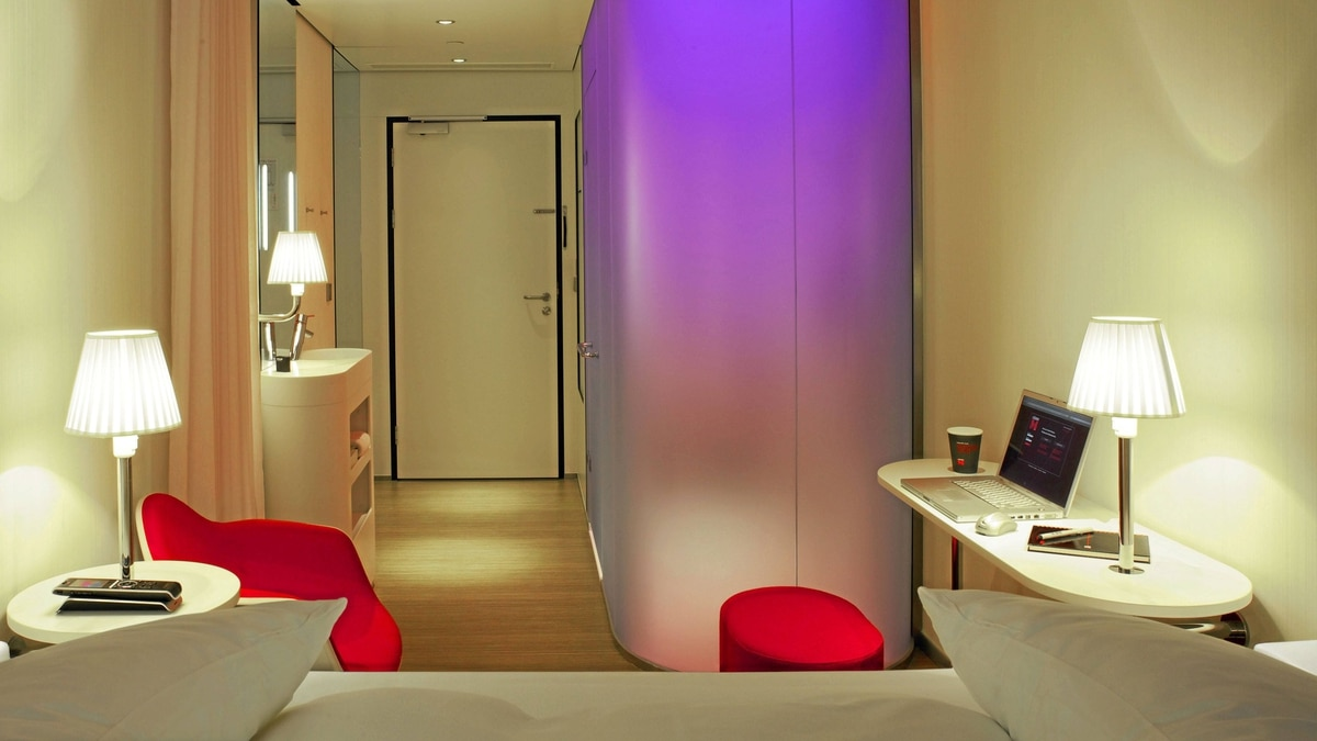 Small but stylish rooms at CitizenM feature a cylindrical centrepiece: a frosted-glass shower and toilet cubicle.