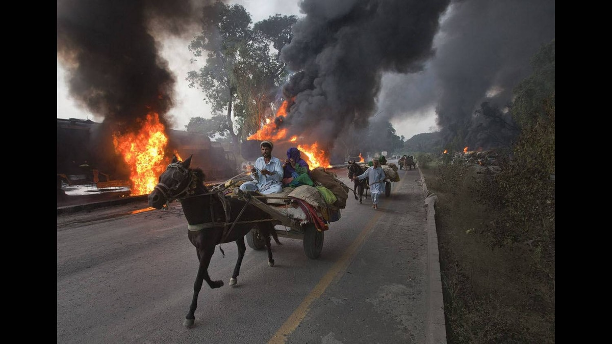 Residents on horse-led carts hurry past burning fuel tankers along the GT Road near Nowshera, located in Pakistan's Khyber-Pakhtunkhwa Province, October 7, 2010.