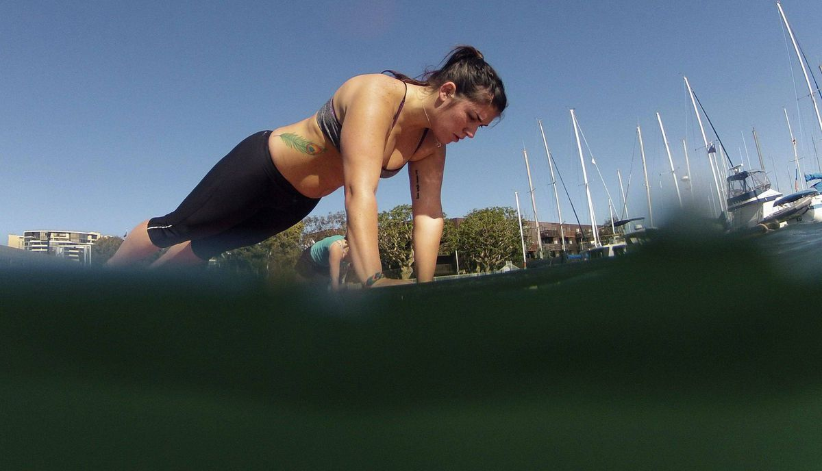 Megan Daws, 25, holds a pose during a Yogaqua class, which combines yoga and paddleboarding, in Marina Del Rey, Los Angeles January 28, 2012.