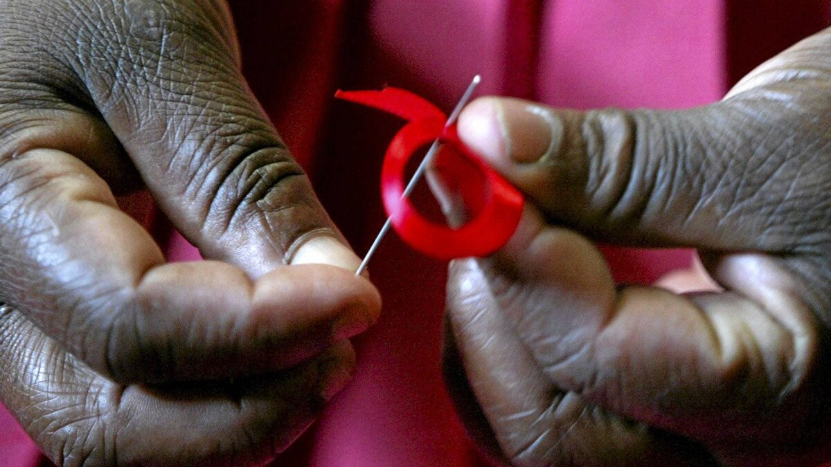 A Kenyan woman prepares ribbons for World Aids Day.