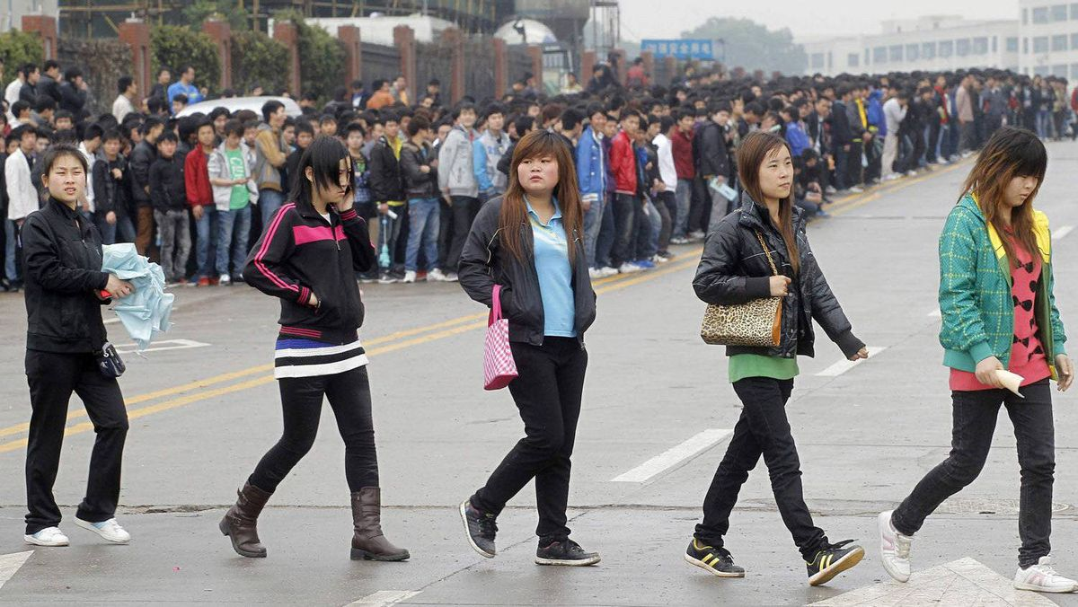 Job seekers cross a road as they queue outside Foxconn recruitment center in Shenzhen, Guangdong province February 22, 2012. Apple's top manufacturer in China, Foxconn Technology, is having no problems luring fresh workers to churn out ever more gadgets, despite the firm's reputation as a tough employer that has put it under a thorough probe into its labour practices. Picture taken February 22, 2012.