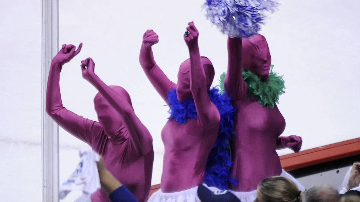 Vancouver Canucks fans dressed in purple suits dance in the crowd during Game 5. REUTERS/Andy Clark