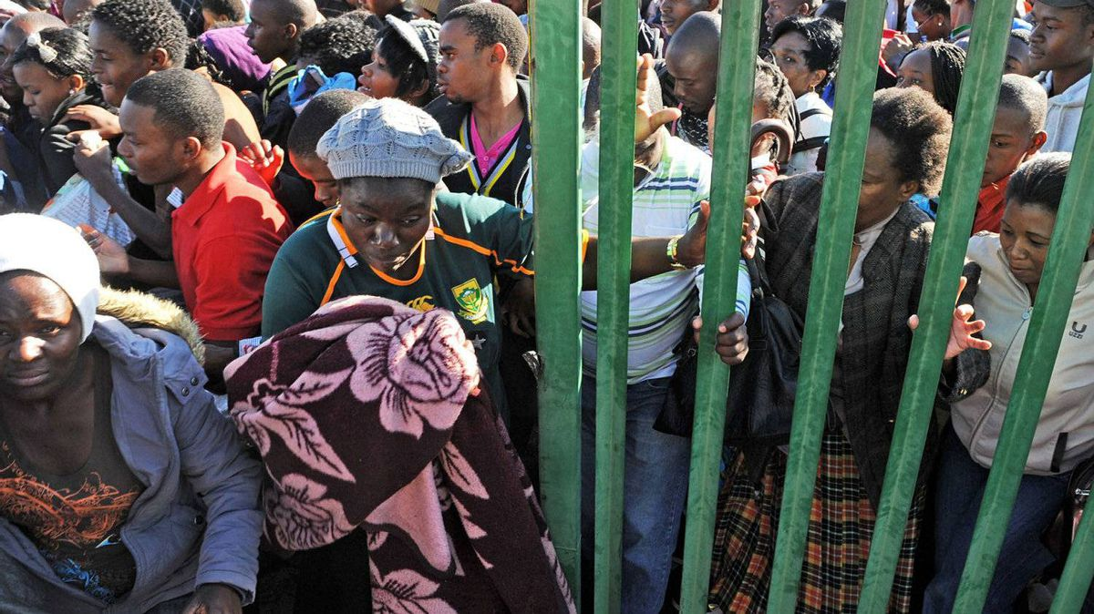 Thousands of young students and their parents push their way into the gates causing a stampede at the University of Johannesburg, South Africa, Tuesday Jan. 10, 2012. Prospective students stampeded at the gate of a university Tuesday, leaving one person dead and two others seriously injured, officials said.