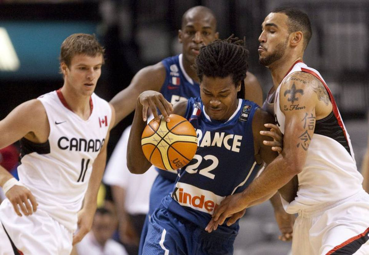 Team France's Mickael Gelabale, second from right, drives against Team Canada's Robert Sacre, right, during the first half of exhibition FIBA basketball action in Toronto Friday, August 13, 2010.