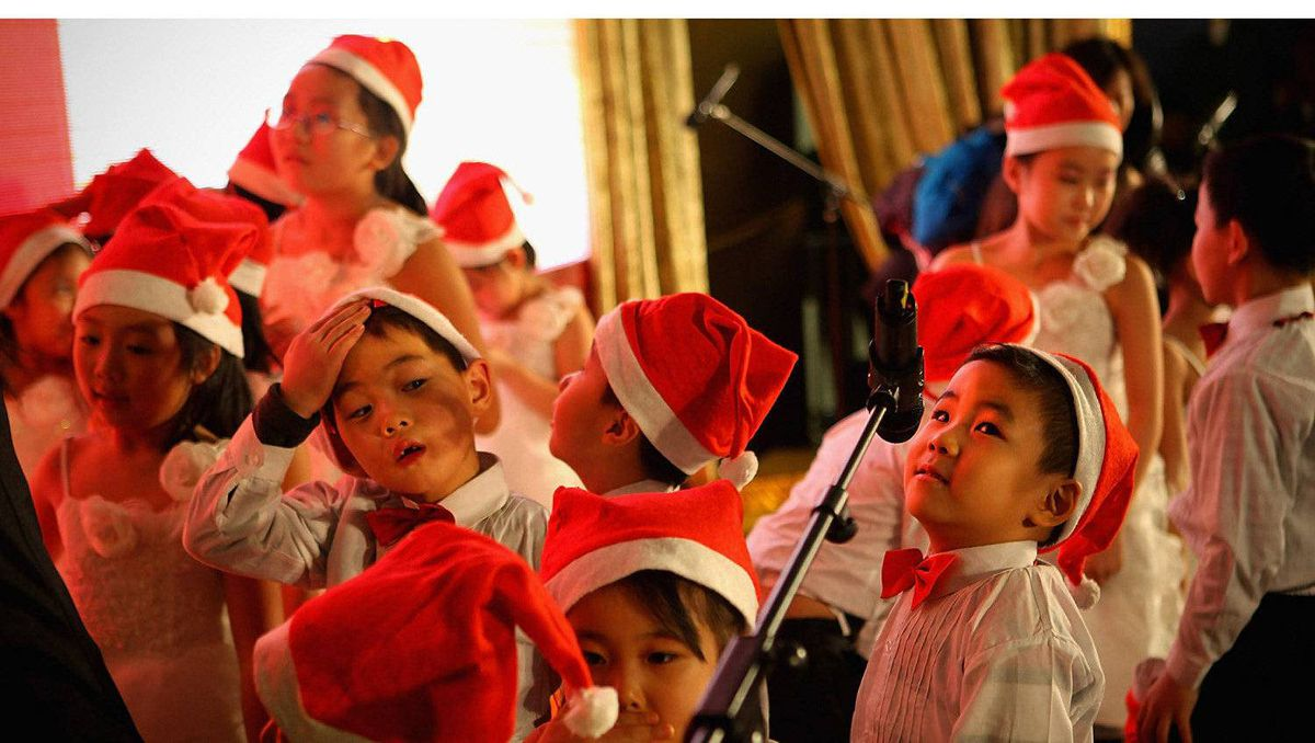 Chinese children rest after singing Christmas songs for customers at a shopping center on Christmas Eve December 24, 2011 in Beijing, China. Though Christmas is not officially celebrated in China, the holiday is becoming increasingly popular as Chinese adopt more Western ideas and festivals.