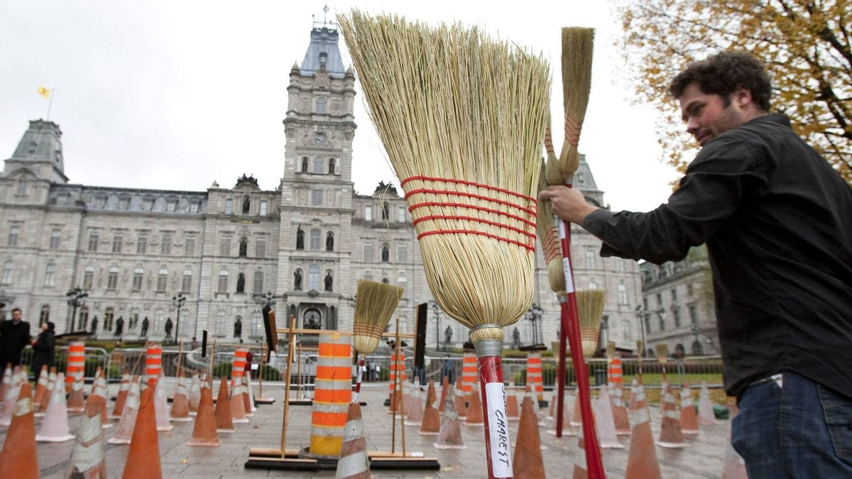 A protester installs brooms on road construction signs while asking for a public inquiry in the Quebec construction industry on Oct. 18, 2011 at the legislature in Quebec City.